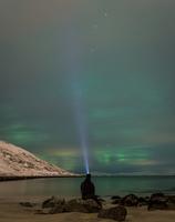 Man sitting on lakeshore and looking at Aurora Borealis, Hammerfest, Norway