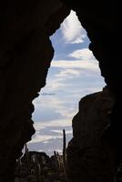 A volcanic cave frames a flooded Salar de Uyuni, Bolivia