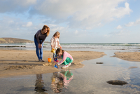 Mum and Daughters playing by the sea waters edge