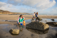 Mother and Daughters playing in a rock pool on the beach 11098066491| 写真素材・ストックフォト・画像・イラスト素材|アマナイメージズ