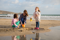 Mother and Daughters playing by the sea waters edge