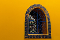Close-up of yellow wall and blue window with traditional decorations