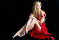 Studio portrait of beautiful woman in red dress sitting