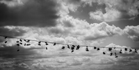 Shoes hanging from wire against clouds