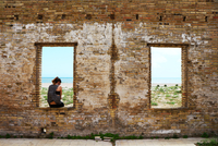 Portrait of woman sitting in window of abandoned building