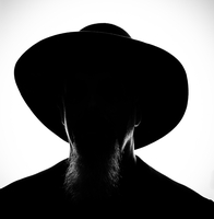 Dark headshot portrait of man in cowboy hat with beard