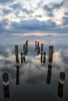 Posts of pier ruins in sea at sunset