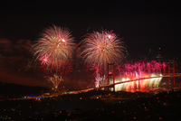 Fireworks display over suspension bridge in city