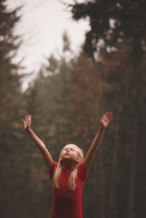 Portrait of girl (8-9) in forest with arms raised