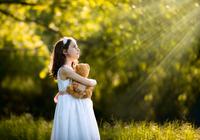 Portrait of girl in white dress holding teddy bear in grass 11098069035| 写真素材・ストックフォト・画像・イラスト素材|アマナイメージズ