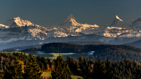 Three snow covered mountain peaks over forest