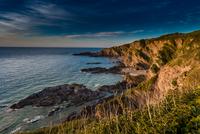 Cliffs on seashore at sunset