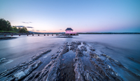 Hut on pier near rocky seashore