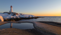 Snowy beach and lighthouse at dawn
