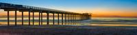 Panorama of pier on beach at sunset