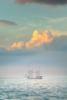 Sunset over sailing ship in sea