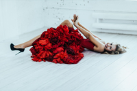 Portrait of woman in red floral dress lying down 11098069354| 写真素材・ストックフォト・画像・イラスト素材|アマナイメージズ