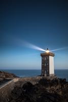Lit lighthouse with stone bridge on seashore