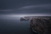 Steep cliffs and sea stacks on seashore in moody weather