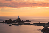 Lighthouse on hill on small island at sunset