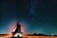 Windmill against starry sky at night