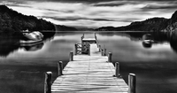 Wooden pier on lake in grayscale