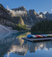 Canoes on pier near mountain peaks and forest