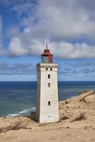 Lighthouse on sandy beach in fair weather