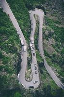 Road bend on mountainside with traffic