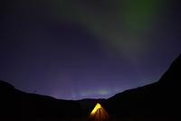 Lit tent under aurora borealis at night