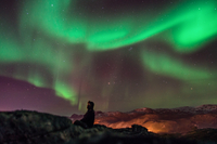 Aurora borealis over person in winter jacket