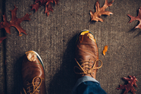 Feet with brown shoes and autumn leaves on floor