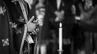 Close-up of priest hands holding cross