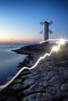 Windmill on rocky beach at sunset