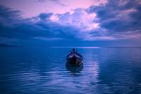 Drifting boat at purple dusk