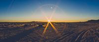 Lens flare over desert at sunset