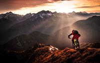 Person riding bicycle on mountain ridge at sunset