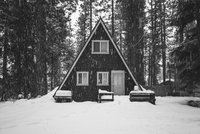 Cabin in forest during snowfall in winter