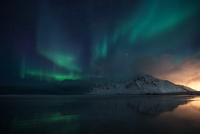 Aurora borealis and stars in sky over mountain