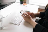 Woman using smartphone at office desk 11098071138| 写真素材・ストックフォト・画像・イラスト素材|アマナイメージズ