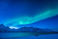 Aurora borealis over mountains and sea