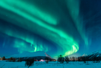 Aurora borealis over snowy plain and mountain