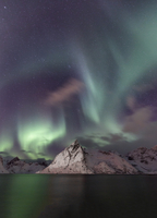 Aurora borealis over snowy mountain on shore