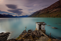 Calm lake and old house at dusk