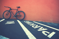Black bicycle leaning on red wall