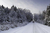 Car driving through winter landscape, Canada