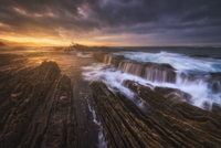 Rocky seaside with waterfalls at sunset, Basque Country, Spain