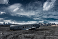 Airplane wreck on beach with mountains in background, Iceland