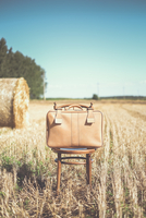 Suitcase on chair in field