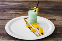 Mint cocktail and mango on plate